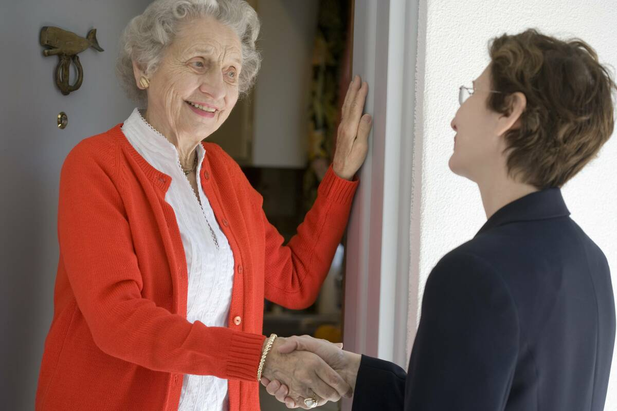 senior woamn shaking hands with salesperson at door